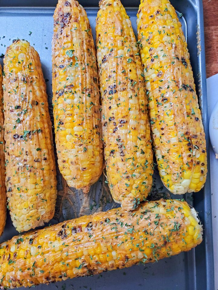 Mexican street corn with a mayo and paprika mixture topped with fresh parsley.