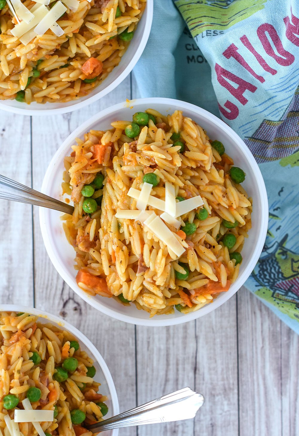 bowl of sweet potato orzo pasta with peas and. shaved parmesan.