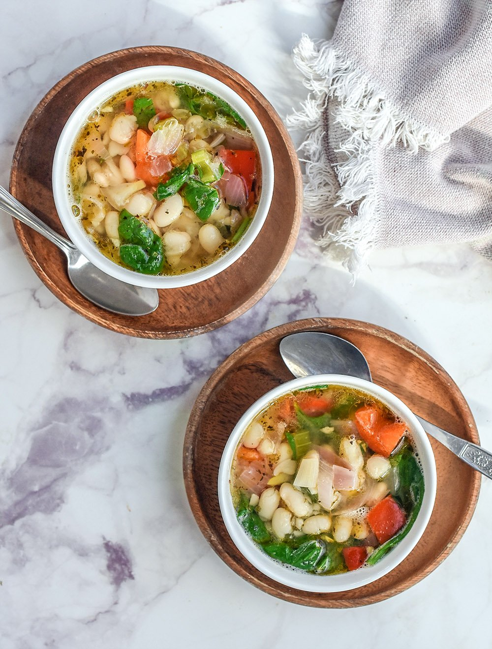 2 bowls of white bean soup loaded with veggies.