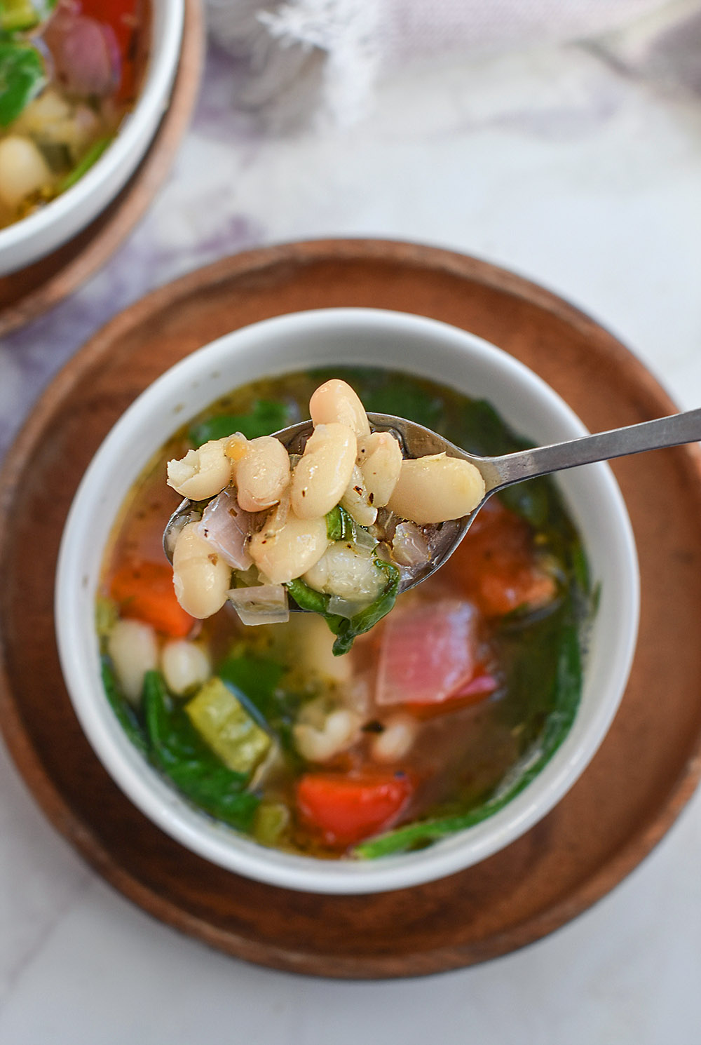 a spoonful of white bean soup full of veggies.
